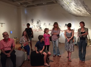 An audience gathered for the curator's talk, including artist Liz Mahood on the far right with her daughter Kate standing beside. Jude Roberts' artwork 'Divine Message' hangs above and the installation 'Carbon Dating' by artists Alison Clouston and Boyd features on the wall behind.