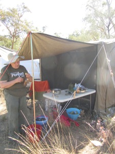 Sue hanging out tea bags to dry with pots of boiled grasses outside her tent - ingredients for future papermaking.